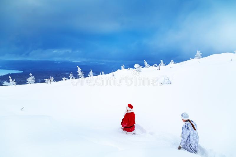 Authentic Santa Claus and a girl in winter clothes are walking on a snowy mountain. Magnificent snowy landscape royalty free stock photo