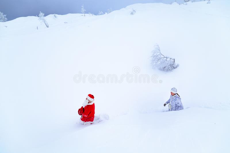 Authentic Santa Claus and a girl in winter clothes are walking on a snowy mountain. Magnificent snowy landscape royalty free stock photography
