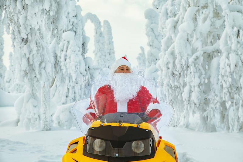 Authentic Santa Claus is riding a snowmobile through the winter stock image