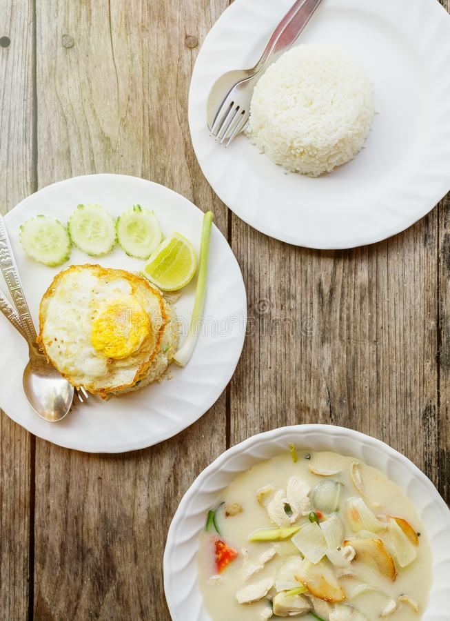Authentic Thai dinner background: Tom kha gai spicy soup, plain rice and pad kra pao with fried egg on top on wooden table at loca stock image
