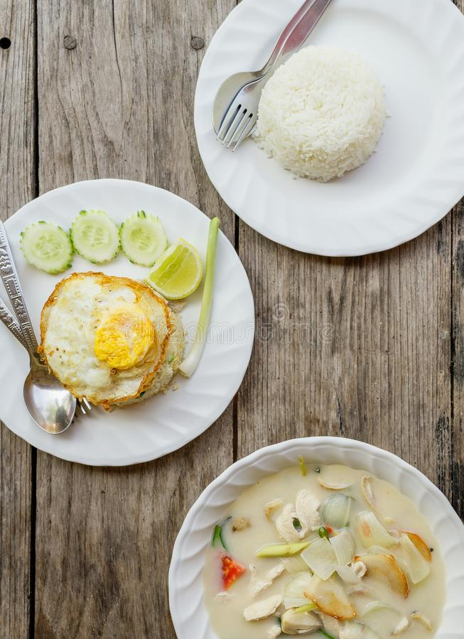 Authentic Thai dinner background: Tom kha gai spicy soup, plain rice and pad kra pao with fried egg on top on wooden table at loca royalty free stock photo
