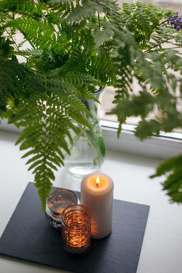 Authentic Tranquil Atmosphere. Kinfolk Hygge Slow Living Style. Candle in candlestick on stone plate on windowsill and fern stock photo