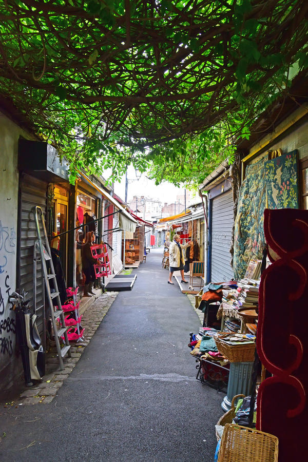 An authentic view of Marche aux Puces de Saint-Ouen, Paris, France. With trees growing naturally between 2 shops on an alley creating a natural shade. This stock images