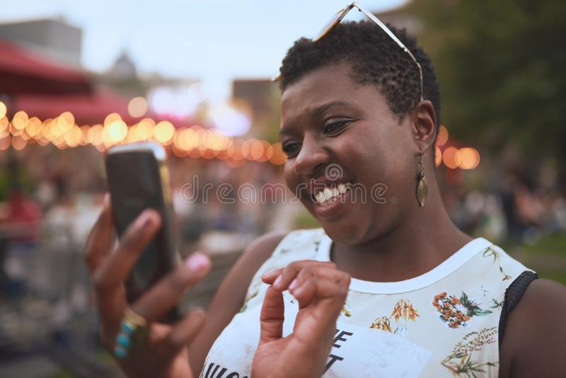 Authentic young african american woman using a mobile phone at a summer music festival royalty free stock image