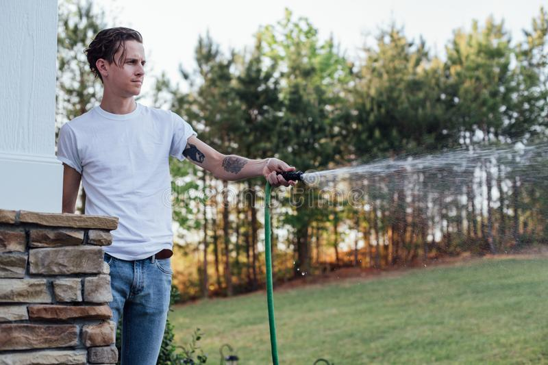 Hipster young man waters the lawn royalty free stock photo