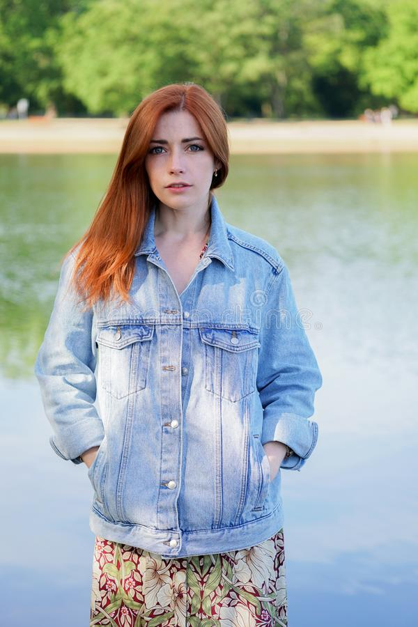 Authentic young woman wearing denim jacket over summer dress standing by lake royalty free stock image