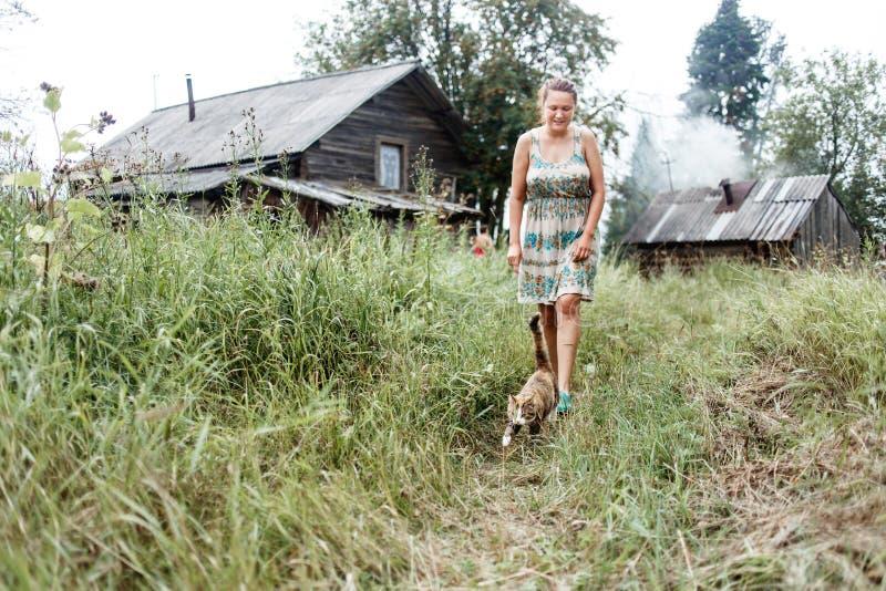 Authentiek landelijk beeld van het lopen van kat, vrouw, en oud logboekhuis met het verwarmen van bad stock foto's