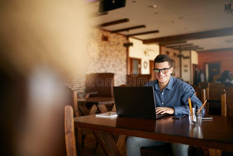 Authentiek portret van jonge glimlachende zakenman die camera met laptop in koffie bekijken Hipster zoals de mens in modieus royalty-vrije stock foto