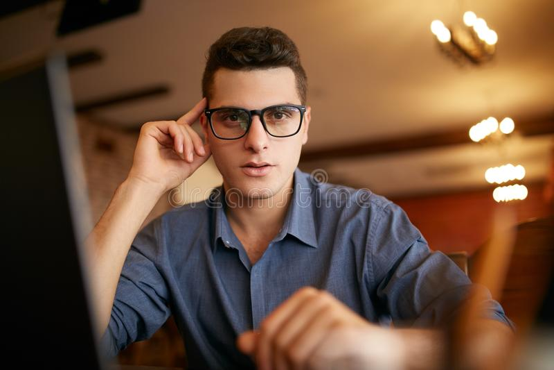 Authentiek portret van jonge zekere zakenman die camera met laptop in bureau bekijken Hipstermens in glazen en stock fotografie
