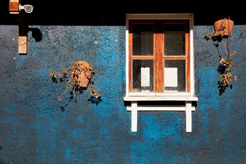 Authentiek raamkozijn van een landelijk plattelandshuisje met concrete donkere blu royalty-vrije stock afbeeldingen