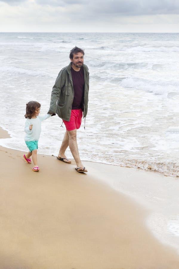 Authentieke foto over vader en dochter die op het strand w lopen stock afbeeldingen