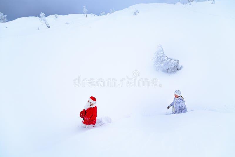 Authentieke Santa Claus en een meisje in de winterkleren lopen op een sneeuwberg royalty-vrije stock fotografie