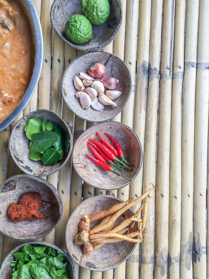 Authentieke Thaise rode kerrie voorbij recept met ingrediënten in kokosnotenshells op bamboelijst stock afbeelding