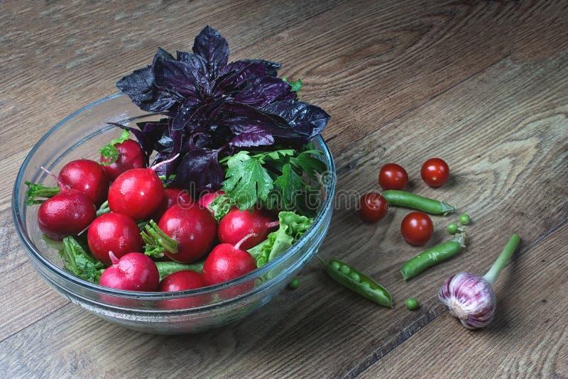 Authentieke vers geplukte knoflook en basilicumbladeren van het tuinbed, in een vergiet, naast bonen, knoflook en kersentomaten  stock fotografie
