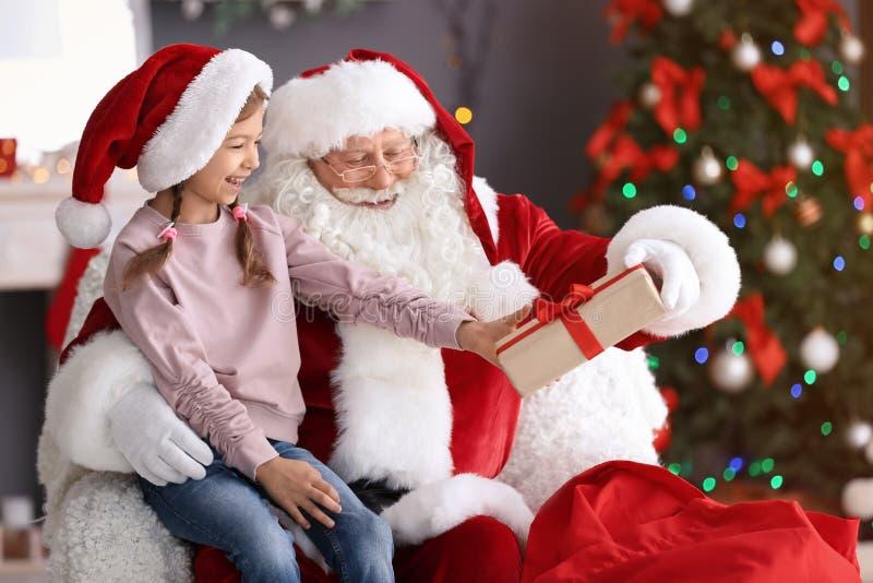 Authentische Santa Claus, die dem kleinen Mädchen Geschenkbox gibt stockfoto