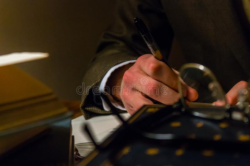 Author writing in journal while surround with books. Author brainstorming ideas for new novel and stories while surrounded by books and a pair of glasses royalty free stock photos