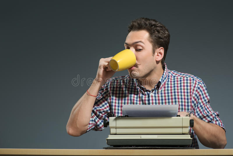 Author drinking coffee at typewriter. Author at work. Close-up of creative young author working at the typewriter and drinking coffee while sitting at his royalty free stock image