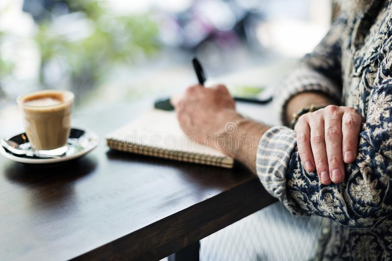 An author making notes in a coffee shop royalty free stock photography