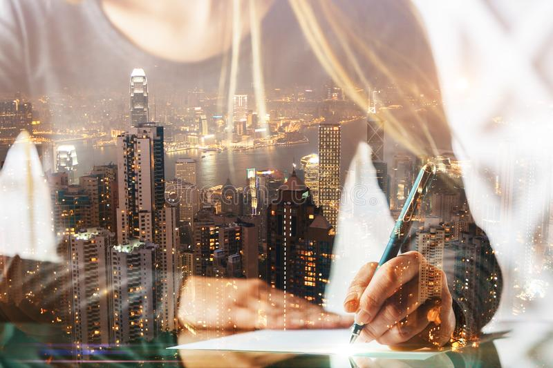 Author and occupation concept. Close up of businesswoman hands doing paperwork or writing letter at abstract desk with city view. Author and occupation concept stock images