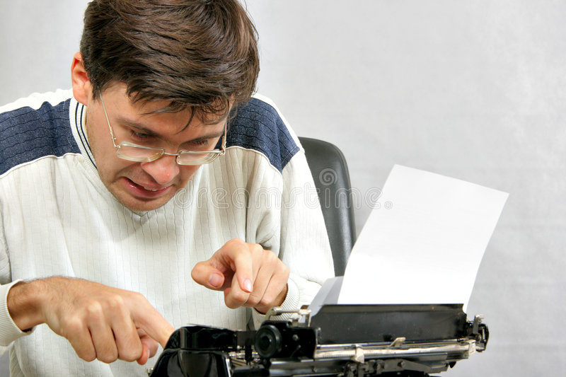 Author typing his bestseller. Author types a bestseller on a vintage typewriter stock photography