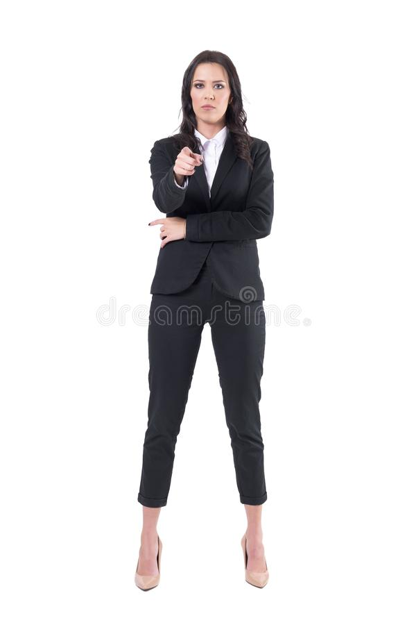 Authoritative business woman in formal suit pointing finger and showing at you. Full body isolated on white background stock image