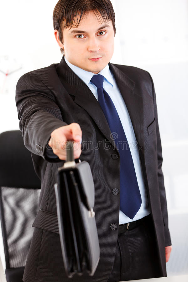 Authoritative businessman giving briefcase. Authoritative business man standing at office desk and giving briefcase. Close-up royalty free stock images