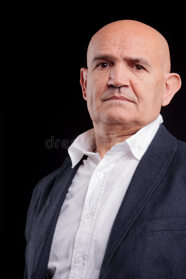 Authoritative businessman. Portrait of an authoritative mature businessman with a bald head, black studio background royalty free stock photo