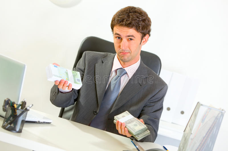 Authoritative businessman sitting at desk. Authoritative modern businessman sitting at office desk and offering money packs royalty free stock photo