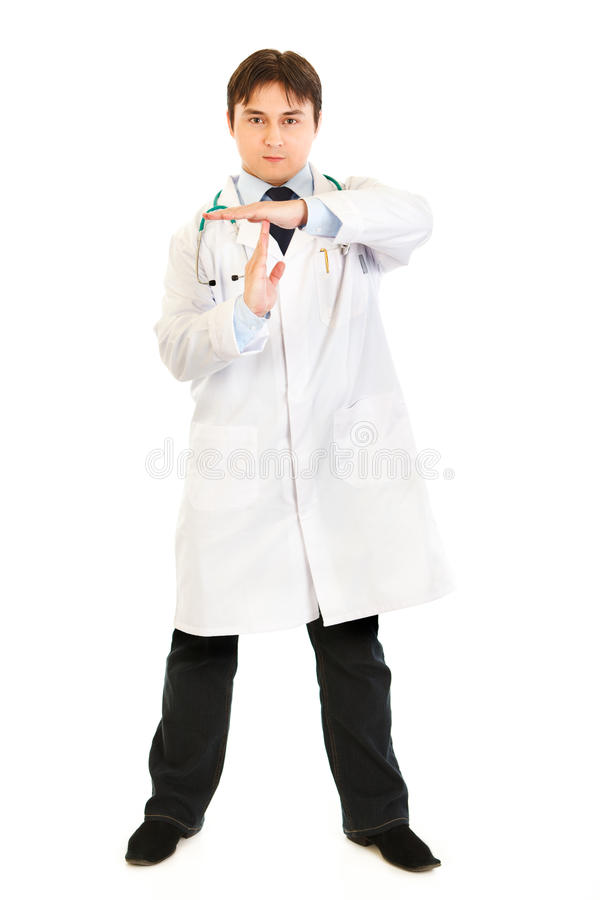 Authoritative doctor with time out crossed arms. Authoritative medical doctor with time out crossed arms isolated on white royalty free stock image