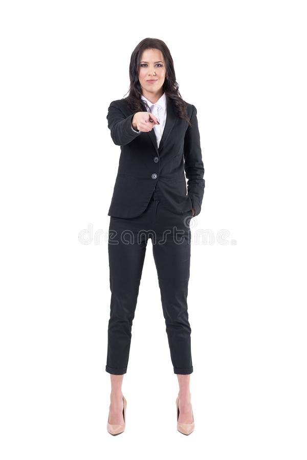 Authoritative female business manager pointing finger at you looking at camera with forced smile. Full body isolated on white background royalty free stock photography
