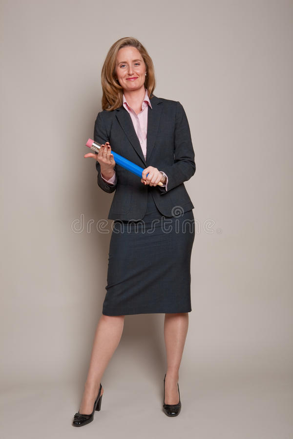 Authoritative woman. Tapping oversized pencil on hand royalty free stock photos