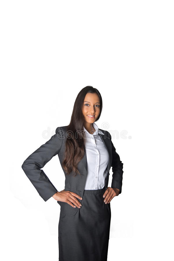 Authoritative young businesswoman. Standing watching the camera at an angle with her hands on her hips and smile of satisfaction, isolated on white stock photos