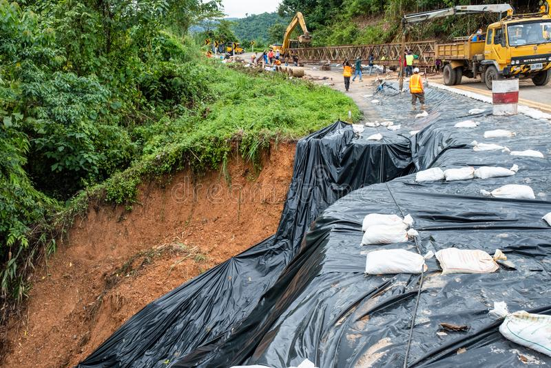 Authorities repairing the collapsed road landslide. Nan, Thailand - Aug 04 2018 : Authorities repairing the collapsed road landslide in valley stock photo