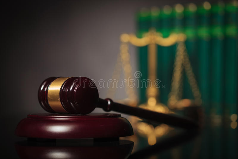 Authority of the legal system concept. Judge's hammer in front of books and scale in the background stock photography