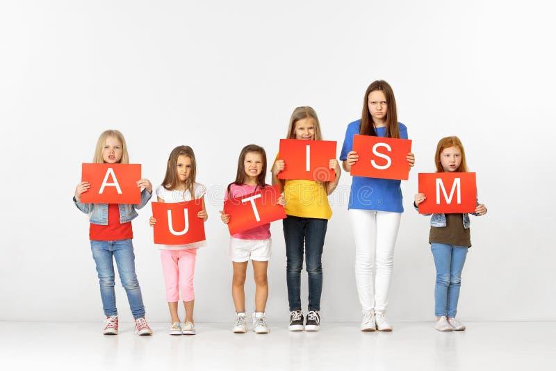 autism Gruppo di bambini con le insegne rosse isolate nel bianco fotografia stock libera da diritti
