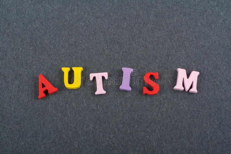 AUTISM word on black board background composed from colorful abc alphabet block wooden letters, copy space for ad text. Word on black board background composed stock photo