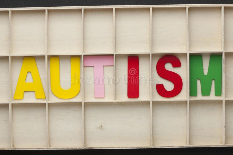 Autism Word Concept. The word Autism spelled with colorful alphabet letters on wooden surface royalty free stock photos
