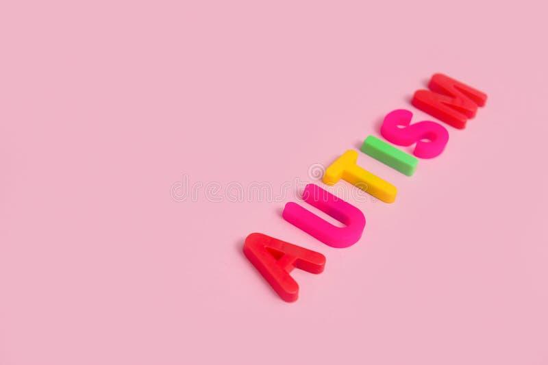 AUTISMO da palavra no fundo cor-de-rosa, vista superior foto de stock