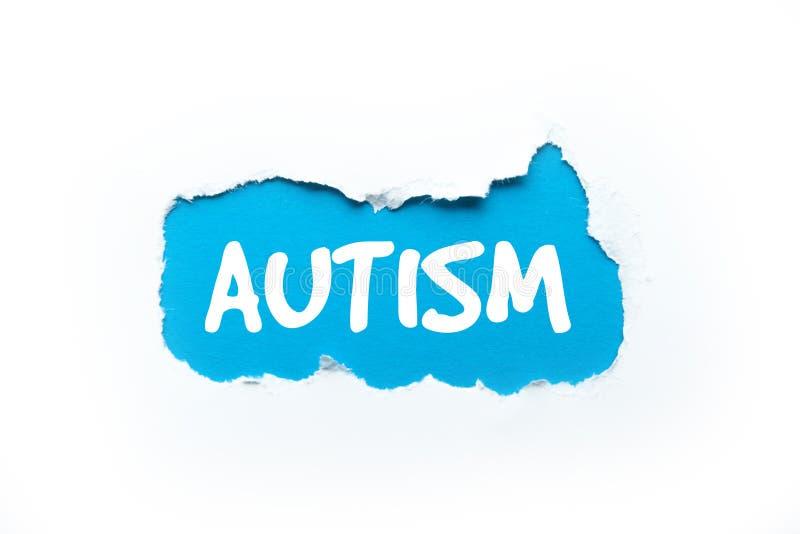 Autismo, la palabra en un fondo blanco rasgado foto de archivo