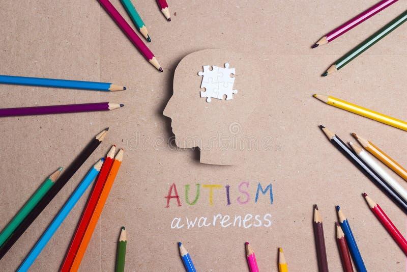 Autismus-Bewusstseins-Tageskonzept mit Puzzlespielgehirnsymbol- und -farbbleistiften stockbilder