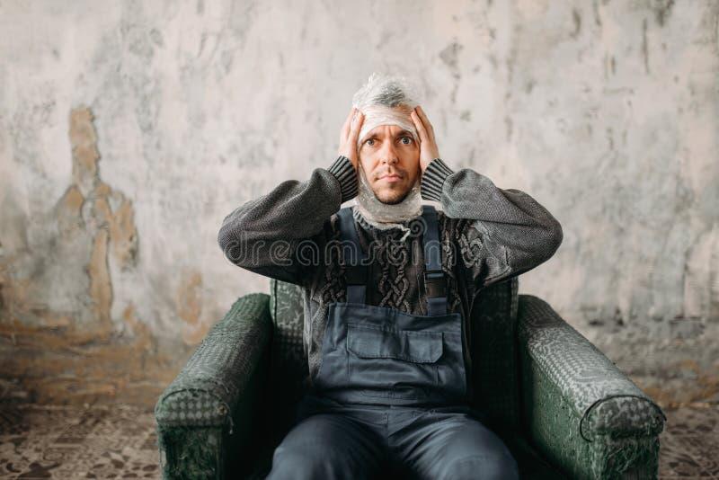 Autist avec le film de bout droit sur la tête se reposant sur la chaise image stock