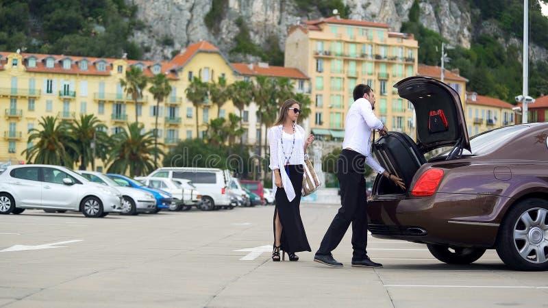 Autista che mette bagagli nel tronco, servizio dell'automobile dell'elite per la gente di affari fotografie stock