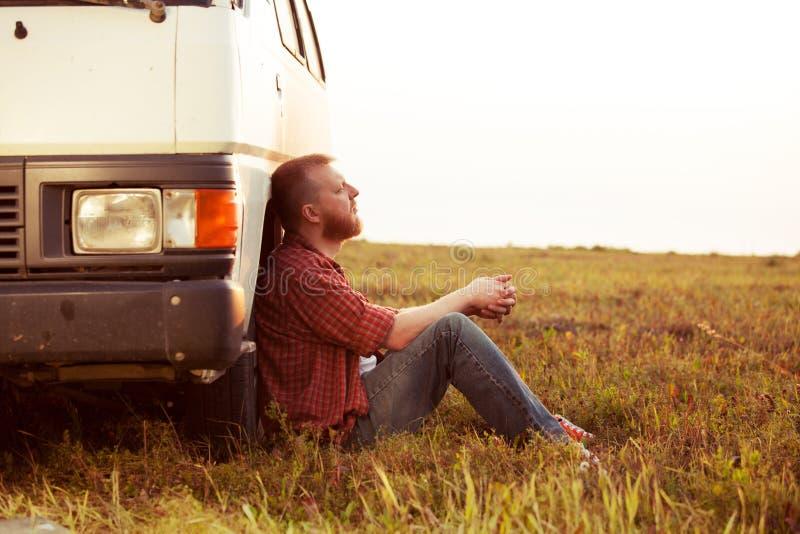 Autista che riposa in un campo vicino alla sua automobile immagine stock libera da diritti