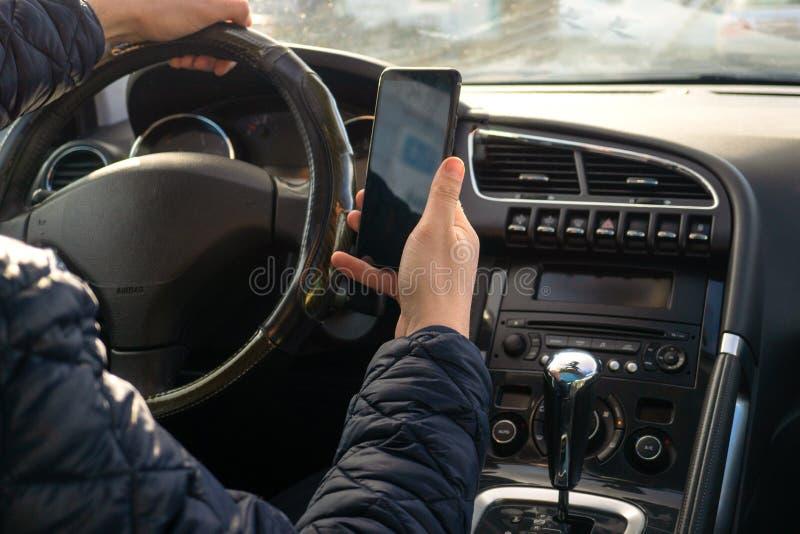 Autista dell'uomo che utilizza Smart Phone nell'automobile fotografia stock