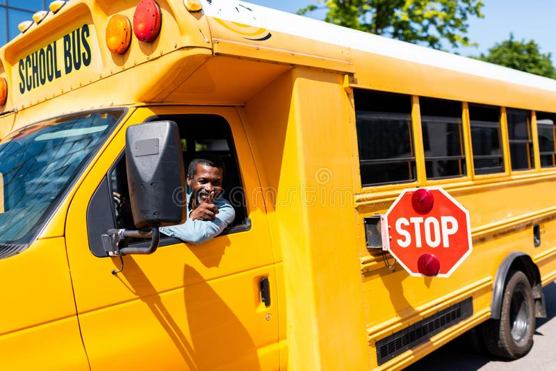 autista di autobus afroamericano maturo sorridente che guarda fuori finestra immagini stock