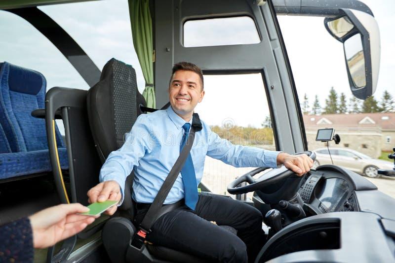 Autista di autobus che prende biglietto o carta dal passeggero immagini stock libere da diritti