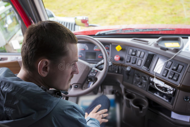 Autista di camion in carrozza del camion dei semi con il cruscotto moderno fotografia stock libera da diritti
