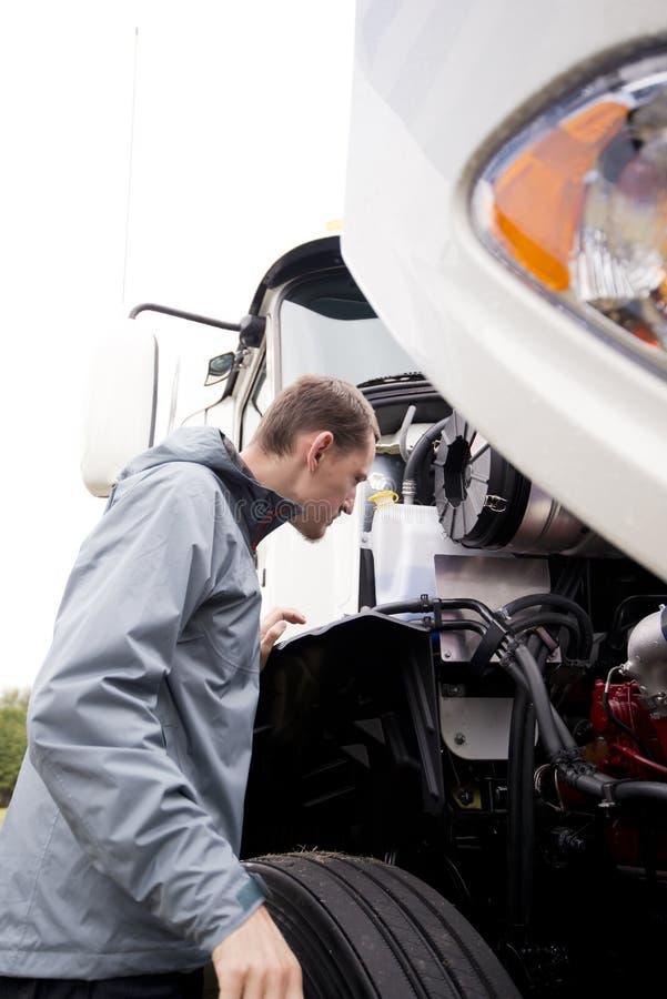 Autista di camion che ispeziona il grande motore bianco del camion dei semi dell'impianto di perforazione fotografia stock libera da diritti