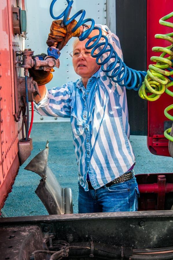 Autista di camion della donna che collega le linee aeree immagine stock libera da diritti