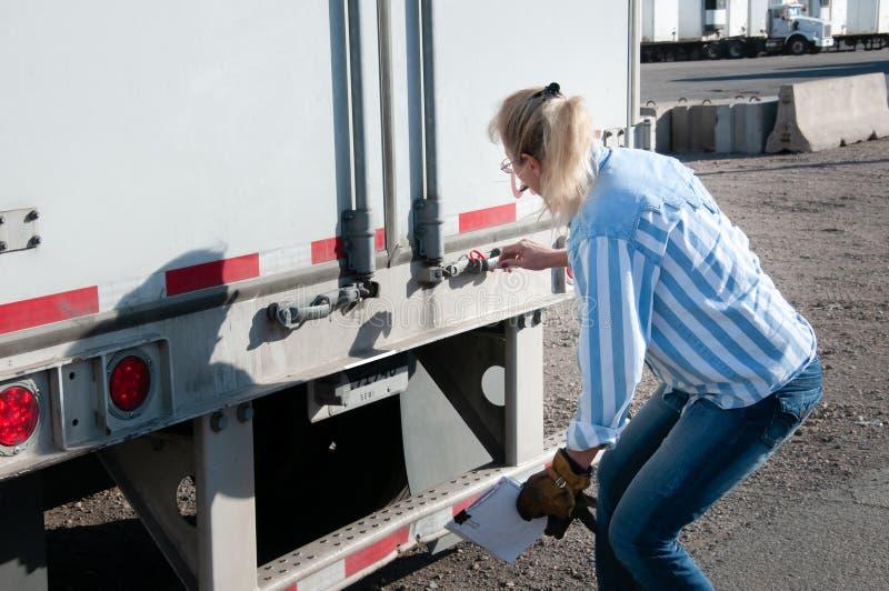 Autista di camion della donna che controlla il suo numero della guarnizione del rimorchio immagini stock libere da diritti